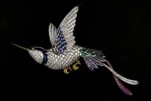 MAGNÍFICO BROCHE EN FORMA DE COLIBRÍ. Oro blanco de 18 K. con contrastes españoles utilizados a partir de 1934. En forma de colibrí con gran cuajado de brillantes, zafiros azules, esmseraldas, amatistas y rubíes. Patas de oro amarillo de 18 K. Salida: 16.000 €.